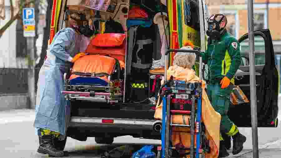 Com máscaras, paramédicos ajudam a transportar um paciente em Estocolmo durante a nova pandemia de coronavírus - Jonathan NACKSTRAND / AFP