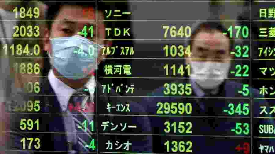 Pedestres observam índices na Bolsa de Tóquio - ISSEI KATO