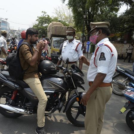 12.abr.2021 - Policial pede que motorista use máscara para proteção contra o coronavírus, em Hyderabad, na Índia; novas infecções pelo coronavírus no país atingiram um nível recorde - Noah Seelam/AFP
