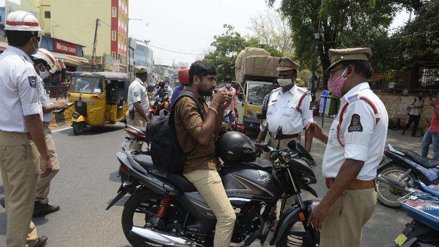 Policial pede que motorista use máscara para proteção contra o coronavírus, em Hyderabad, na Índia - Noah Seelam/AFP