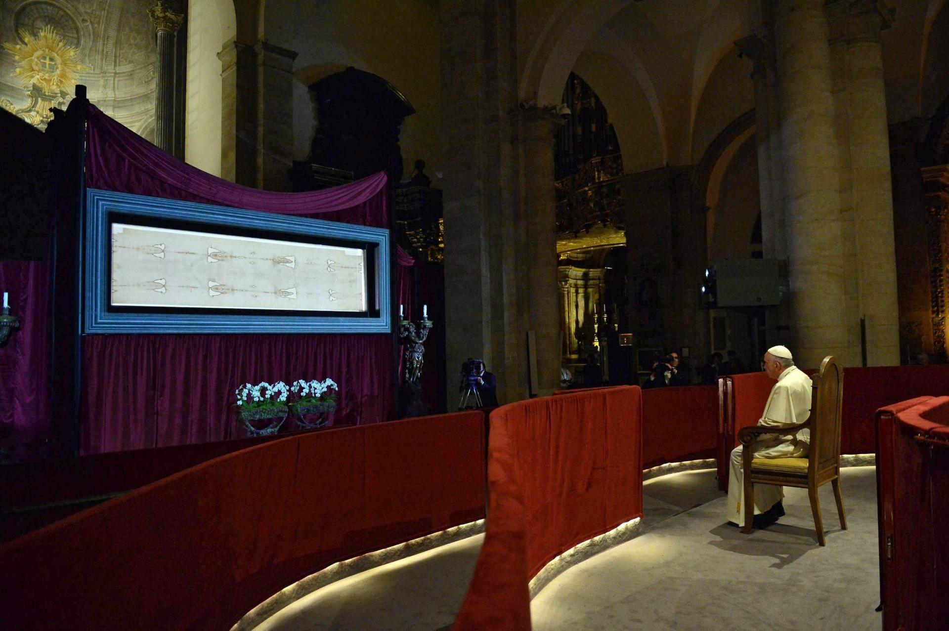 21.jun.2015 - O papa Francisco se senta e reza diante do Santo Sudário, o tecido de pouco mais de quatro metros de comprimento reverenciado por alguns como o pano no qual Jesus Cristo foi sepultado, exposto na Catedral de Turim, no norte da Itália, neste domingo (21)