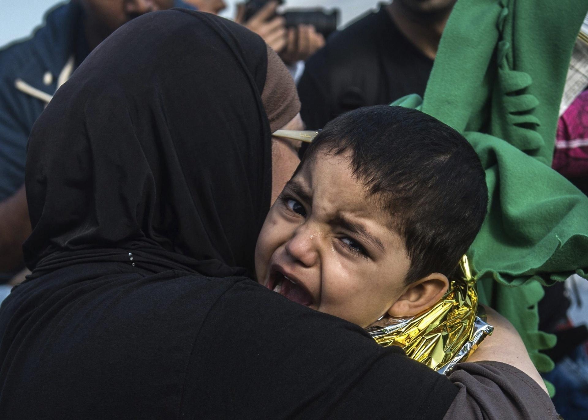 1º.out.2015 - Criança refugiada afegã chora nos braços da mãe durante sua chegada à ilha de Lesbos, na Grécia. Ele e a família vieram a bordo de bote inflável. Cerca de 100 mil refugiados já chegaram na ilha grega desde agosto, segundo a Guarda Costeira do país