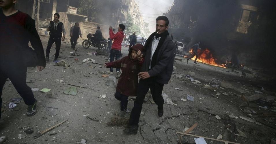 7.nov.2015 - Um homem segura a mão de uma criança enquanto fogem de área que teria sido alvo de um bombardeio aéreo de forças leais ao presidente sírio, Bashar al-Assad, neste sábado, em Douma