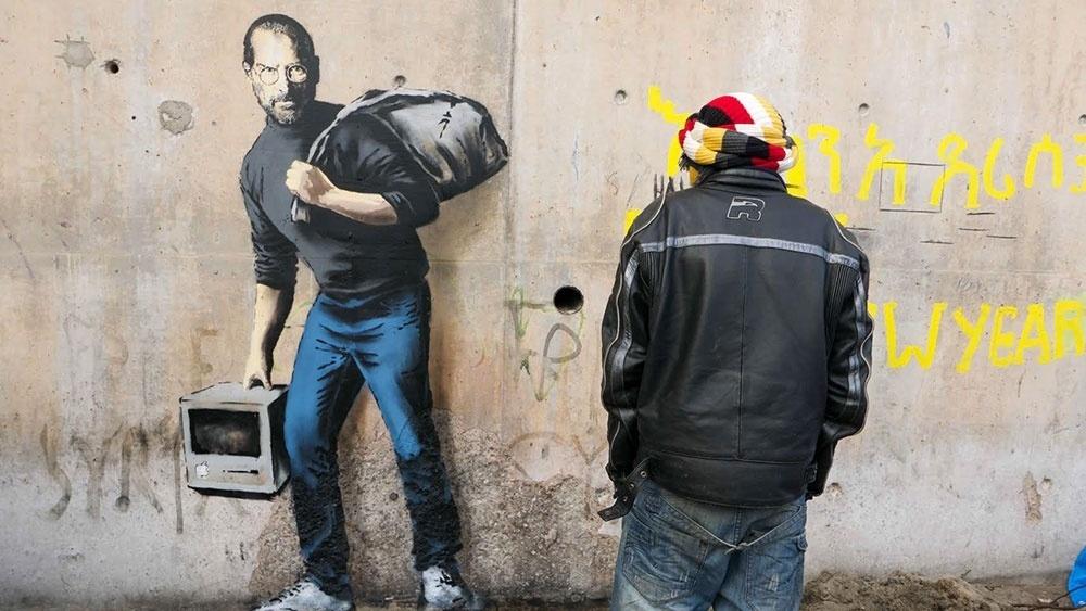 11.dez.2015 - O artista britânico Banksy divulga fotos de seu retrato de Steve Jobs, fundador da Apple, como um refugiado sírio em Calais, na França, onde milhares de refugiados acampam. Jobs era filho biológico de um sírio
