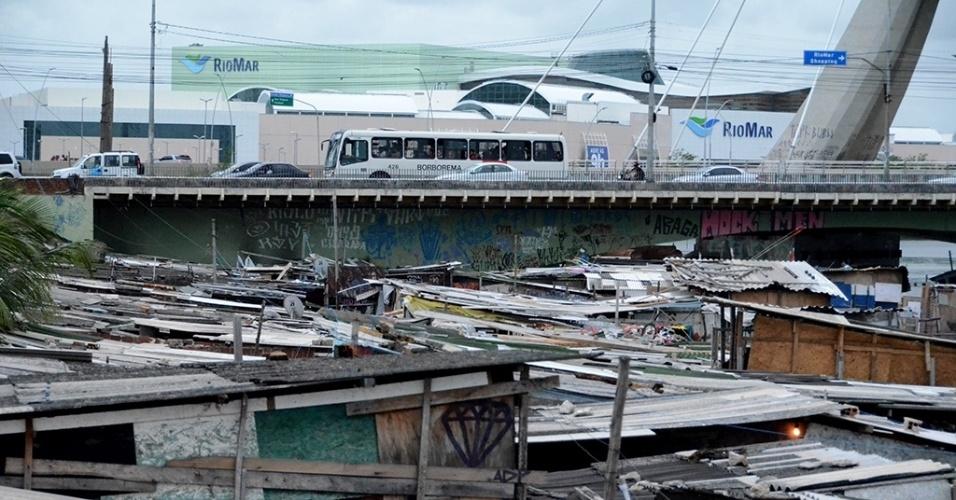 """3.mar.2016 - A comunidade """"favela do Sossego, no bairro do Pina, na região sul do Recife tem cerca de 100 famílias. As casas foram erguidas sob tábuas no rio Capibaribe. No local não há banheiro, coleta de lixo e as visitas de agentes de saúde e de endemias --dizem os moradores--  são raras. Não há também água encanada, e a energia só chega por causas de ligações clandestinas"""