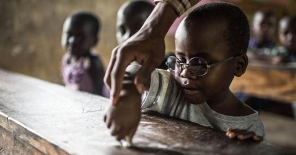 """8.jul.2016 - É o primeiro dia de aula de Criscent. Ele nunca havia visto as letras e precisa aprender o alfabeto do zero. """"riscent perdeu muitos anos de aprendizagem e seu cérebro agora precisa colocar-se em dia com o que vê"""", disse Magyezi"""