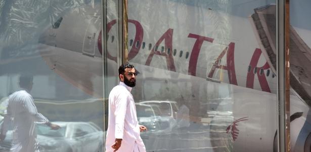 Homem passa diante de anúncio da Qatar Airways em Riad, na Arábia Saudita
