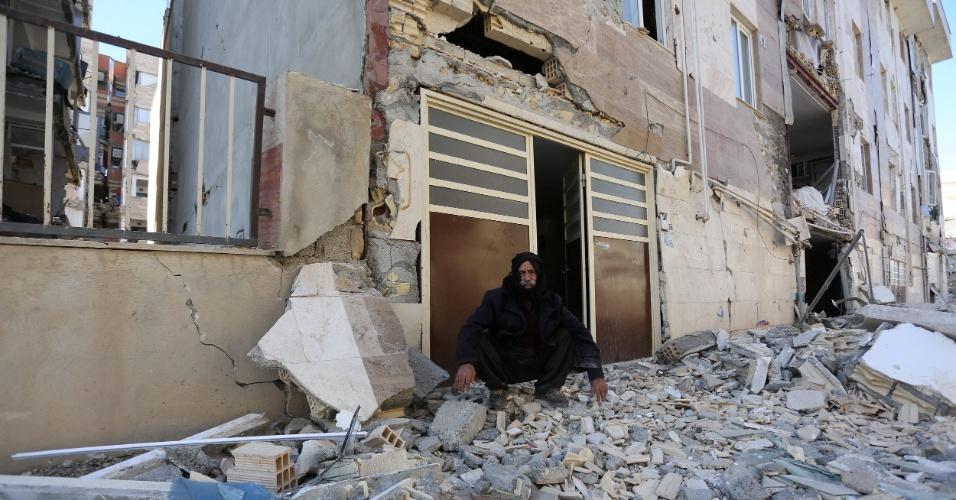 13.nov.2017 - Homem senta diante de entrada de prédio destruído por terremoto em Sarpol-e Zahab, na província de Kermanshah, no Irã