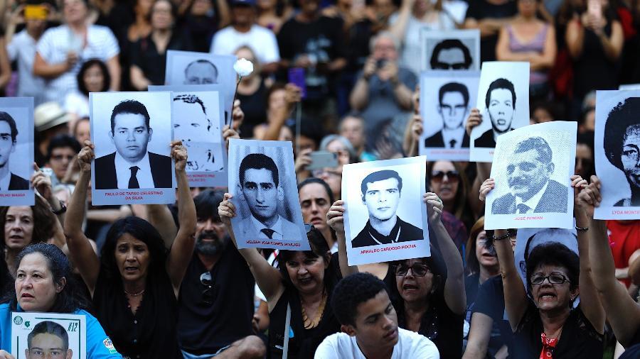 31.mar.2019 - Participantes da Primeira Caminhada do Silêncio pelas Vítimas de Violência do Estado exibem fotos de desaparecidos no Parque do Ibirapuera, em São Paulo - Marcelo Chello/CJPress/Estadão Conteúdo