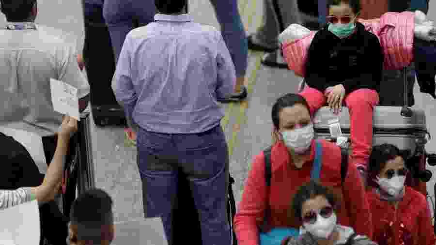 Passageiros com máscara de proteção no aeroporto do Galeão, no Rio de Janeiro - RICARDO MORAES