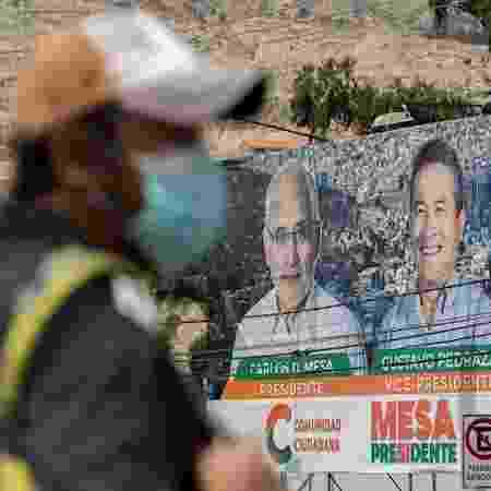 17.out.2020 - Homem passa por cartaz que mostra Carlos Mesa, candidato à Presidência da Bolívia, na cidade de La Paz - Joédson Alves/EFE