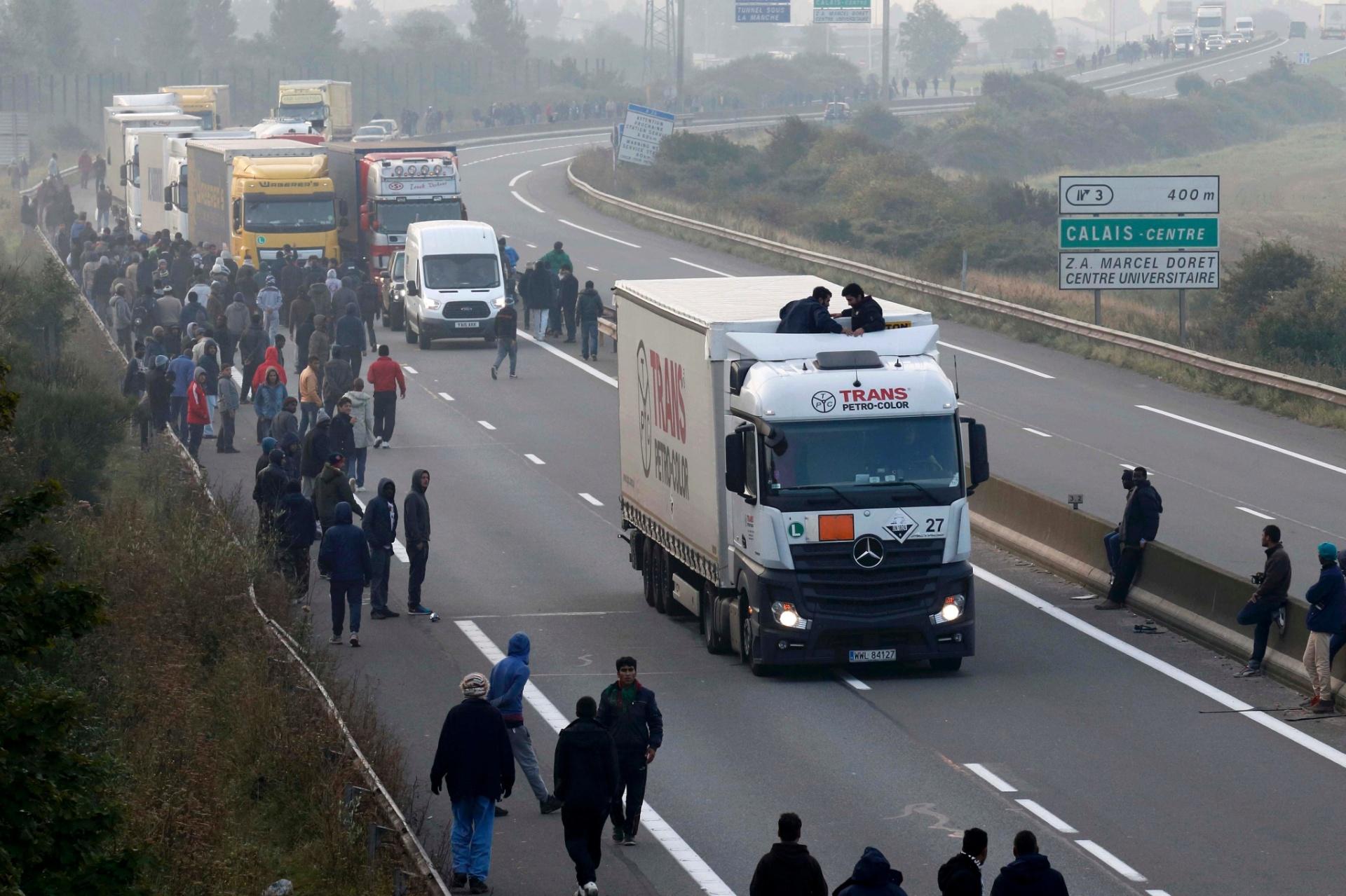 3.out.2015 - Imigrantes se reúnem na estrada que dá acesso ao terminal de ferry boats em Calais (França). Durante a madrugada, cerca de 200 imigrantes entraram no Eurotunnel pela cidade francesa, chocando-se com a equipe e polícia e forçando a suspensão dos serviços. Cerca de 3.000 de refugiados estão acampados no lado francês do túnel em Calais, tentando embarcar em veículos que se dirigem para a Grã-Bretanha
