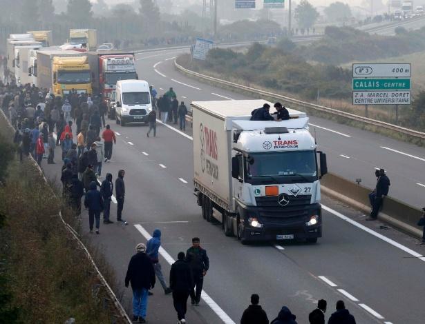 3.out.2015 - Imigrantes se reúnem na estrada de acesso ao terminal de balsas em Calais