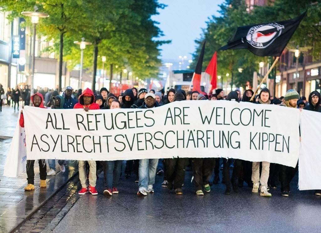 15.out.2015 - Centenas de pessoas participaram de uma manifestação em apoio aos imigrantes com faixa que diz 'Todos os refugiados são bem-vindos', em Hamburgo, na Alemanha. O protesto também era contra o aumento da restrição de asilo para os migrantes