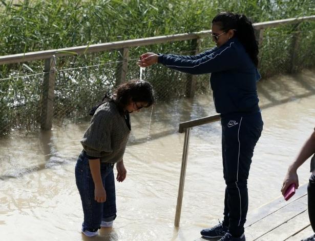 10.jan.2016 - Peregrina católica é batizada nas águas do rio Jordão, onde Jesus teria sido batizado por João Batista, em  Yardenit, no norte de Israel. O local recebe religiosos para batismos em massa