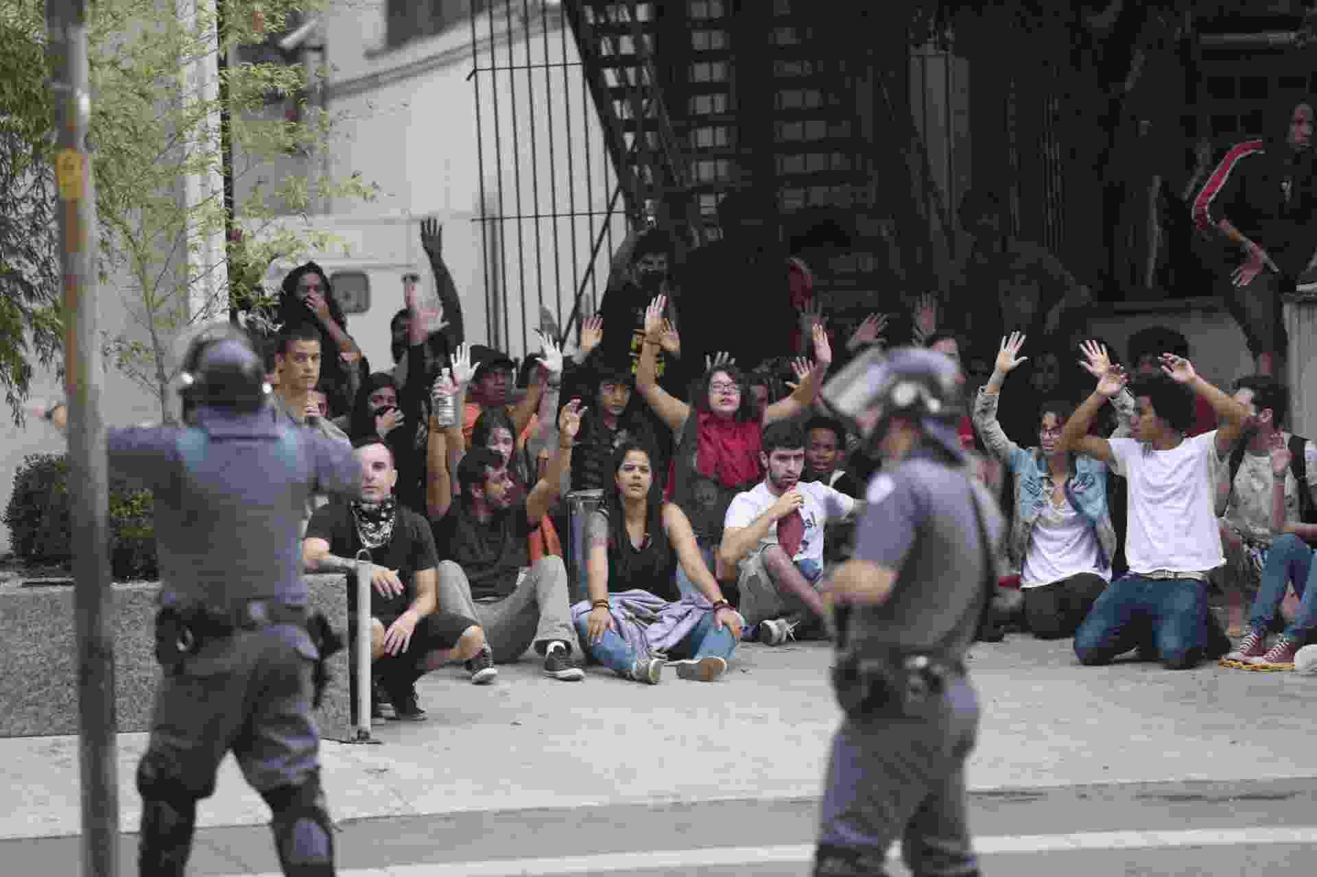 12.jan.2016 - Manifestantes levantam os braços sinal de paz enquanto policiais apontam armas em São Paulo. Protesto contra aumento das tarifas era pacífico quando bombas foram atiradas por policiais - Zanone Fraissat/FolhaPress
