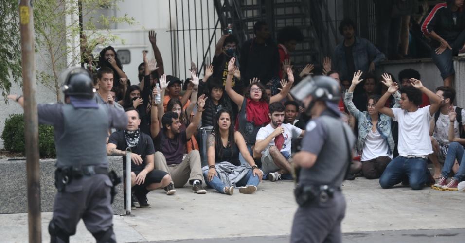 12.jan.2016 - Manifestantes levantam os braços sinal de paz enquanto policiais apontam armas em São Paulo. Protesto contra aumento das tarifas era pacífico quando bombas foram atiradas por policiais