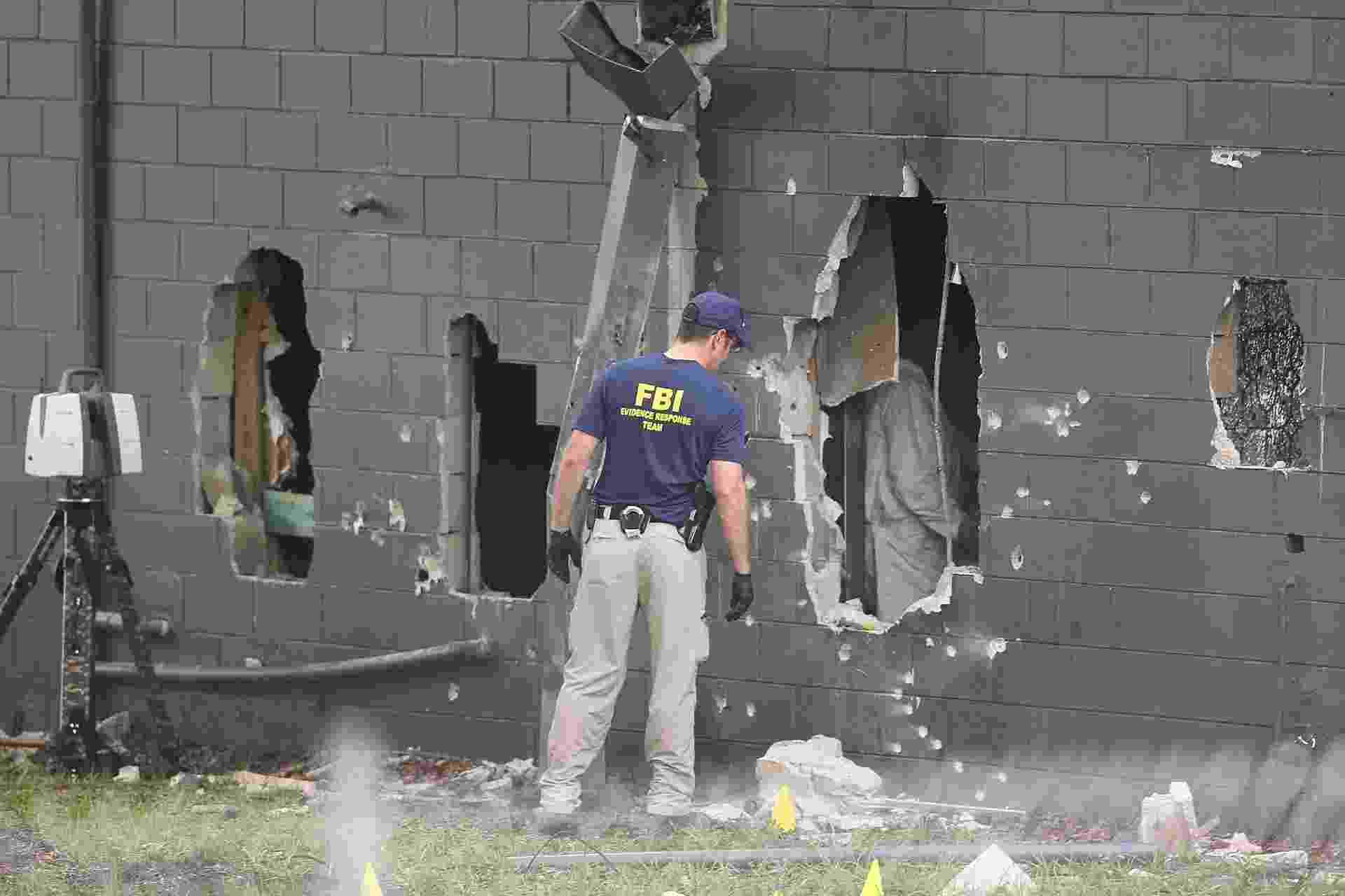 12.jun.2016 - Agentes do FBI inspecionam a parede traseira danificada da boate gay Pulse, onde Omar Mateen, 29, abriu fogo matando 50 pessoas e ferindo 53, em Orlando, na Florida (EUA) - Joe Raedle/Getty Images/AFP