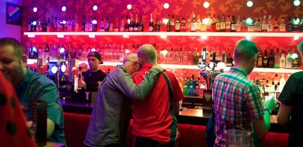 Casal se beija no Delmonicas, um tradicional bar gay em Glasgow, na Escócia