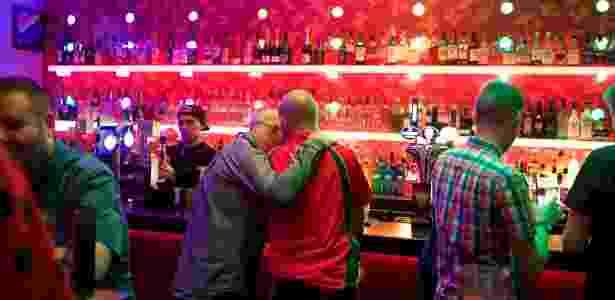 Casal se beija no Delmonicas, um tradicional bar gay em Glasgow, na Escócia - Paulo Nunes dos Santos/The New York Times