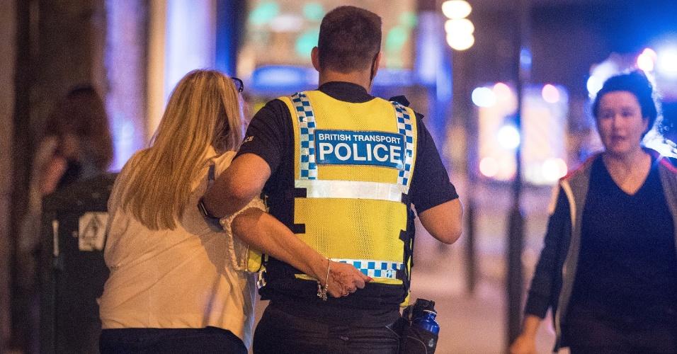 22.mai.2017 - Policial de Manchester ajuda mulher ferida no atentado terrorista