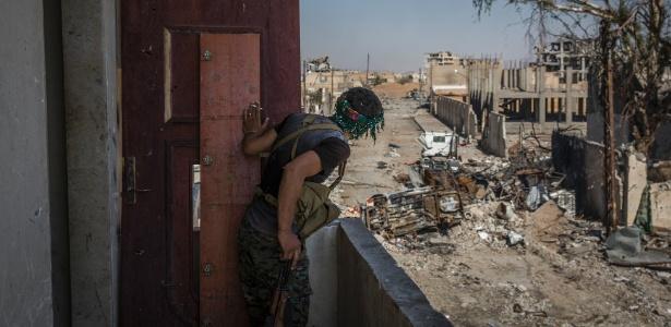 Soldado das Forças Democráticas da Síria espia em direção às ruínas onde são travados combates em Raqqa, na Síria, em foto de 12 de outubro de 2017