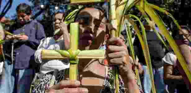 25.mar.2018 - Mulher segura cruz feita com folha de palmeira durante celebração da Semana Santa, em Caracas - Xinhua/Boris Vergara - Xinhua/Boris Vergara