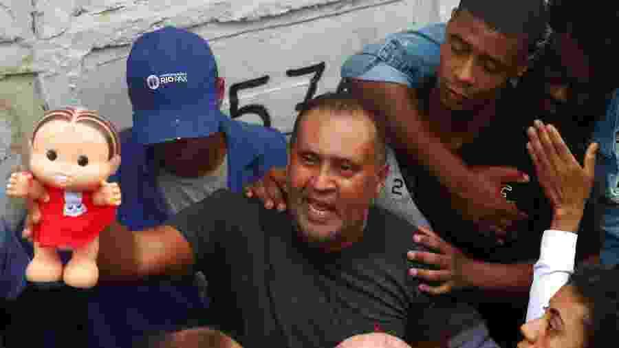 22.set.2019 - Avô de Ághata, Airton Félix segura boneca que pertencia à neta durante enterro no Rio - Pilar Olivares/Reuters