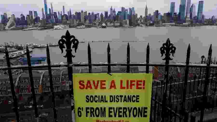 Cartaz promovendo distanciamento social está pendurado em uma cerca no Hamilton Park, acima do rio Hudson, com o horizonte da cidade de Nova York - MIKE SEGAR/REUTERS