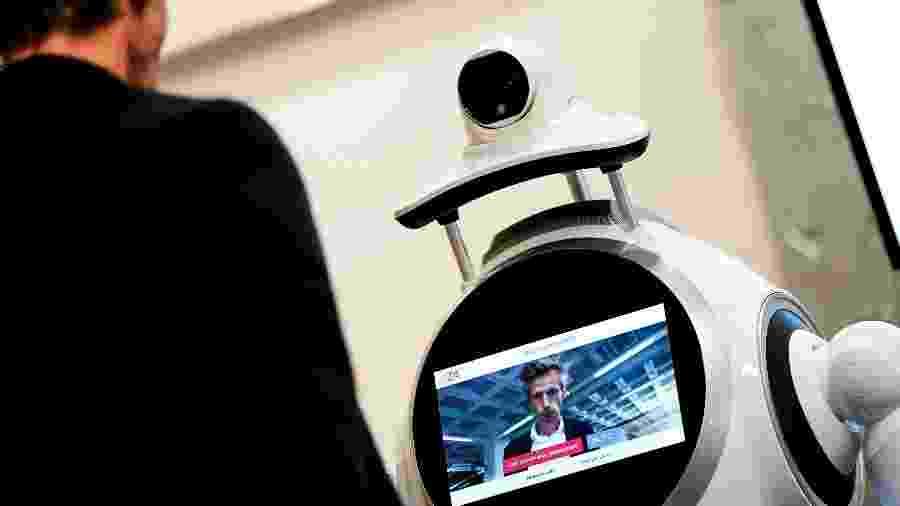 Funcionário da empresa ZoraBots testa robô no hospital da Universidade da Antuérpia. Ele verifica a temperatura dos visitantes e se eles estão usando máscaras - Kenzo Tribouillard - 29.mai.2020/AFP