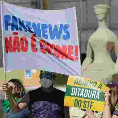 31.mai.2020 - Apoiador do presidente Jair Bolsonaro exibe faixa em que diz que notícia falsa não seria crime em manifestação em Brasília - Dida Sampaio/Estadão Conteúdo