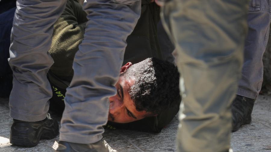 15.jun.2021 - A polícia de Israel detém um palestino durante confrontos que eclodiram antes de uma procissão de jovens de extrema-direita, na Cidade Velha de Jerusalém - REUTERS / Ammar Awad