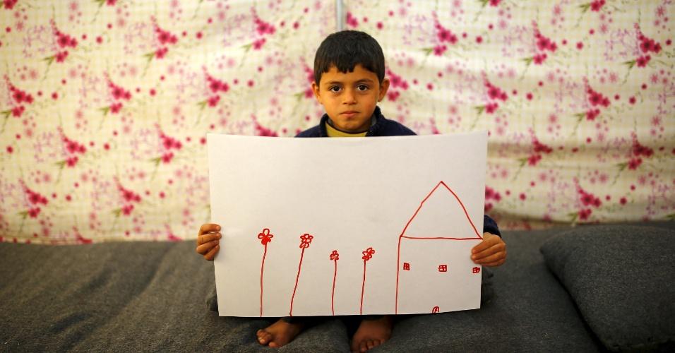 O menino sírio Ali Aadhar, 9, mostra desenho de sua casa na Síria enquanto se senta em sua tenda em no campo de refugiados de Midyat, na província de Mardin, Turquia, onde vive. A guerra civil na Síria, que já deixou centenas de milhares de mortos, empurra outros tantos para o exílio, entre muitos deles crianças. Os desenhos das crianças do acampamento mostram memórias de suas casas, traumas vividos e esperanças para o seu futuro. Dos 2,3 milhões de refugiados sírios que vivem na Turquia, mais da metade são crianças