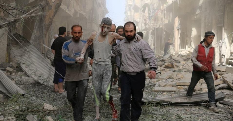 26.abr.2016 - Sírios ajudam um jovem ferido após um ataque aéreo em Aleppo. Pelo menos 17 pessoas morreram, entre elas duas crianças e seis voluntários da Defesa Civil síria