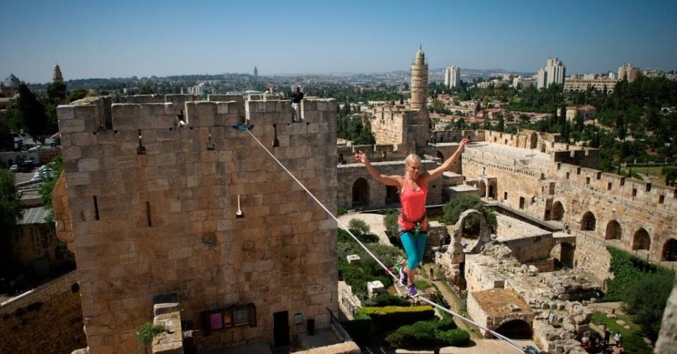 2.mai.2016 - Praticante de slackline, um esporte de equilíbrio sobre uma fita elástica esticada entre dois pontos fixos, atravessa entre duas torres na Cidade Velha de Jerusalém. A americana Heather Larsen atravessou uma linha de 20 metros a uma altura de 35 metros