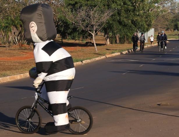 A presidente afastada, Dilma Rousseff (ao fundo, na foto), foi surpreendida por um manifestante vestido de pixuleco montado em uma pequena bicicleta em Brasília