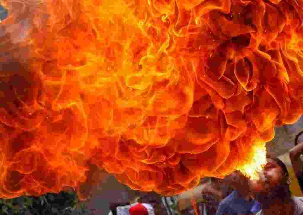 26.jun.2016 - Devoto hindu faz apresentação com fogo durante ensaio para o festival anual Rath Yatra, em Ahmedabad, na Índia. O evento conta com uma procissão que comemora a viagem de carruagem do Deus Jagannath, seu irmão Balabhadra e sua irmã Subhadra. O festival é o único momento em que devotos que não são permitidos dentro dos templos podem ter a chance de ver as divindades, ficando conhecido como uma festa de igualdade e integração - Amit Dave/ Reuters