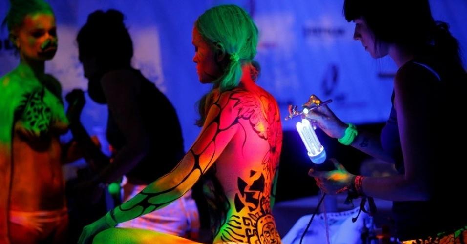 1º.jul.2016 - Pintor corporal usa tinta ultravioleta em modelo durante o Festival Mundial de Bodypainting, em Poertschach, Áustria. O evento é considerado o maior do mundo e deve reunir 300 artistas e mais de 1.500 participantes