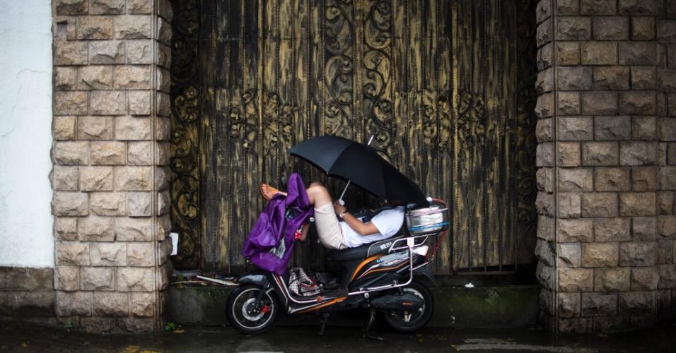 14.jul.2016 - Homem usa um guarda-chuva para se proteger da chuva enquanto tira uma soneca em cima de uma moto em Xangai, na China
