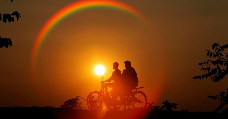 21.nov.2016 - Meninos em silhueta contra o sol, andam de bicicleta nos arredores de Agartala, na India