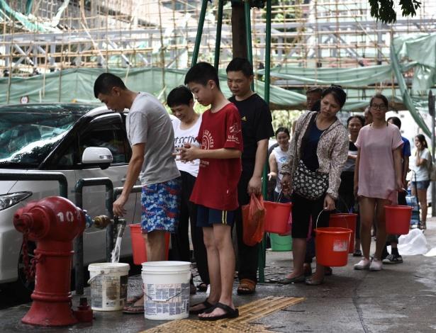 Pessoas fazem fila para coletar água potável em hidrante em Macau nesta quinta-feira