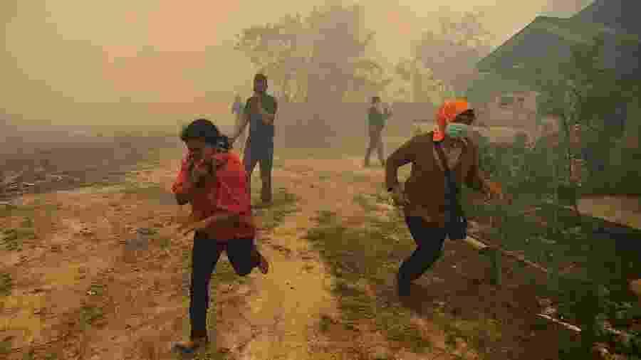 22.set.2019 - Moradores de um vilarejo fogem com a chegada de um incêndio florestal em Kampar, Riau, na Indonésia - Wahyudi/AFP