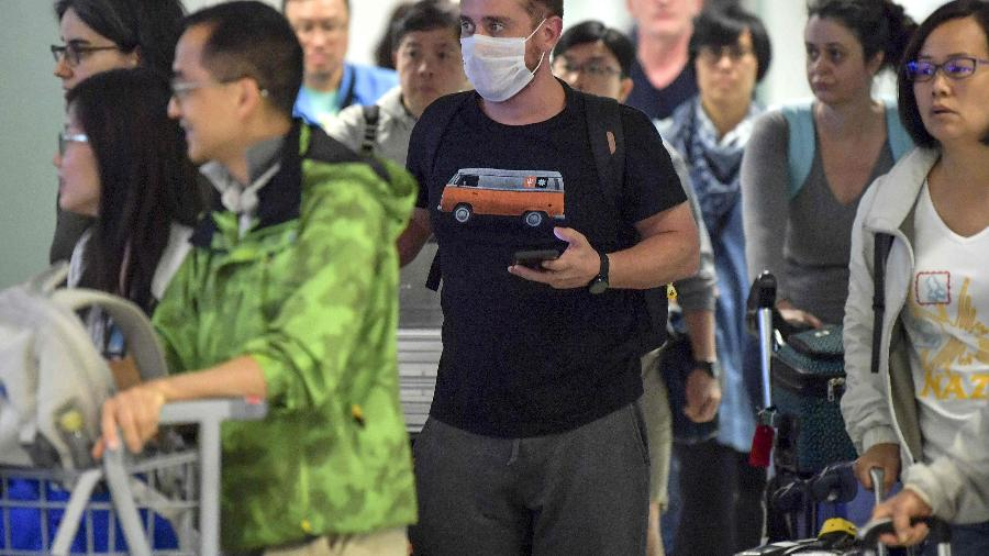 Passageiro usa máscara ao desembarcar no Aeroporto Internacional de Guarulhos, em São Paulo - NELSON ALMEIDA / AFP