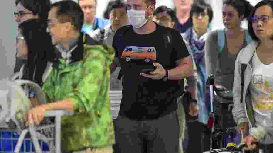 26.fev.2020 - Passageiro usa máscara ao desembarcar no Aeroporto Internacional de Guarulhos, em São Paulo - Nelson Almeida/AFP