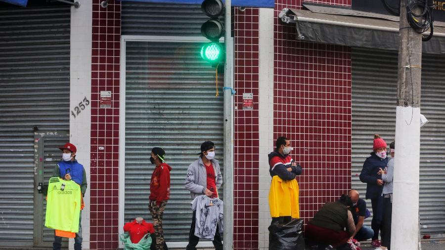 Ambulantes atuam diante de comércio fechado nas ruas do Brás, no centro da capital paulista  - Ricardo Matsukawa/UOL