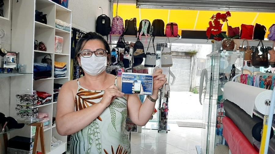 Empreendedora exibe adesivo que informa o e-dinheiro como forma de pagamento digital - Rede Paulista de Bancos Comunitários