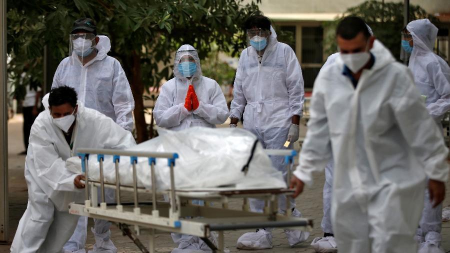 Profissionais de saúde transferem corpo de vítima da covid-19 do IML em Ahmedabad, na Índia - REUTERS/Amit Dave