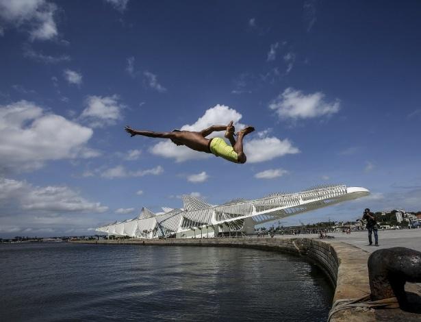 Jovem pula na água na praça Mauá, na baía de Guanabara, no Rio de Janeiro