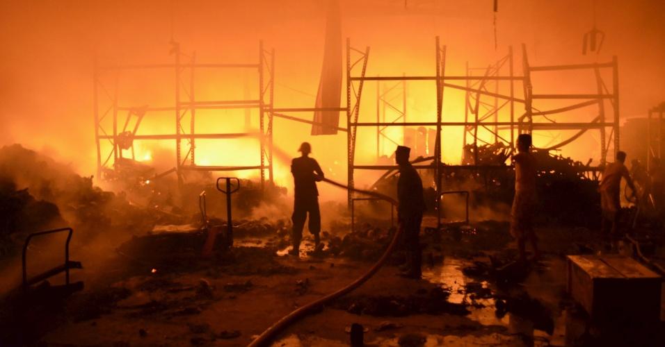 6.jan.2016 - Bombeiros trabalham para conter incêndio em depósito de alimentos destruído por ataque da coalizão liderada pela Arábia Saudita na cidade portuária de Houdieda, no Iêmen