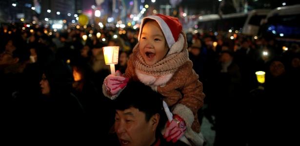Criança nos ombros do pai segura vela durante protesto em Seul - Kim Hong-Ji/Reuters